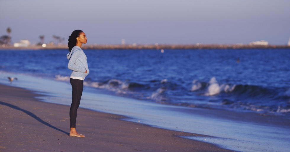 Black woman enjoying the ocean view until waves come